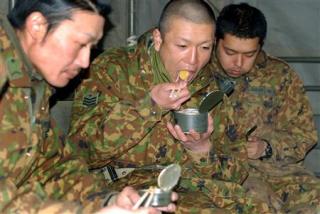 被災者に炊き出し後、冷たい缶詰の食事を取る自衛隊員